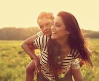 Uśmiechnięta dzieciak dziewczyna śmia się na szczęśliwej cieszy się matce na s z powrotem Obraz Stock
