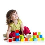 Uśmiechnięta dzieciak dziewczyna bawić się budynków sześcianów zabawki Zdjęcia Royalty Free