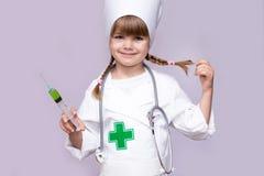 Uśmiechnięta dzieciak dziewczyna bawić się lekarkę z strzykawką na bielu zdjęcie stock