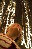 Uśmiechnięta dziecko dziewczyna pod miastowym drzewem zawijającym w górę Xmas sznurka prowadzącego z zaświeca zdjęcie royalty free
