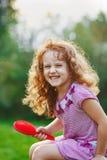 Uśmiechnięta dziecko dziewczyna szczotkuje jej włosy Fotografia Stock