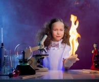 Uśmiechnięta dziewczyn przedstawień substanci chemicznej sztuczka - podpala w palmie Obrazy Stock