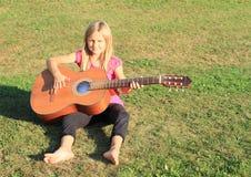 Uśmiechnięta dziewczyna bawić się gitarę Obraz Stock