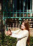 Uśmiechnięta dziewczyna bierze fotografię z jej telefonem komórkowym Zdjęcie Stock