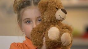 Uśmiechnięta dziewczyna chuje za misiem i bawić się na kamerze, szczęśliwy dzieciństwo zbiory