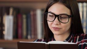 Uśmiechnięta dziewczyna cieszy się trzcinową opowieść w bookstore zbliżeniu zdjęcie wideo