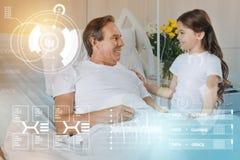 Uśmiechnięta dziewczyna dotyka ramię jej ojciec gdy odwiedzający on w szpitalu fotografia royalty free