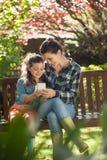 Uśmiechnięta dziewczyna i macierzysty używa telefon komórkowy podczas gdy siedzący na drewnianej ławce Zdjęcie Royalty Free