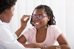 Uśmiechnięta dziewczyna Jest ubranym Eyeglasses Przed Optometrist obrazy royalty free