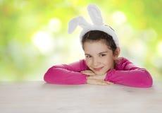 Uśmiechnięta dziewczyna jest ubranym królików ucho przy stołem na abstrakcjonistycznym tle zdjęcia royalty free