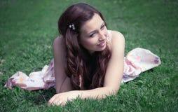 Uśmiechnięta dziewczyna która siedzi na trawie zdjęcie stock