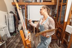 Uśmiechnięta dziewczyna maluje na kanwie z nafcianymi kolorami w warsztacie Fotografia Royalty Free
