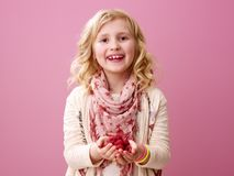 Uśmiechnięta dziewczyna odizolowywająca na różowym tle pokazuje malinki zdjęcie stock