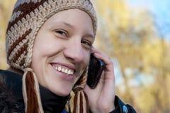 Uśmiechnięta dziewczyna opowiada na telefon komórkowy Zdjęcie Stock