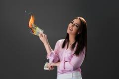 Uśmiechnięta dziewczyna pali pieniądze Pojęcie ekstrawagancja