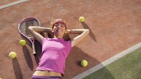 Uśmiechnięta dziewczyna relaksuje na tenisowym sądzie z mnóstwo kantem i piłkami zbiory wideo