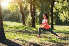 Uśmiechnięta dziewczyna robi lunges w parku Obraz Stock