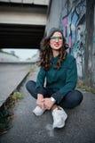 Uśmiechnięta dziewczyna siedzi na autostradzie pod mostem na tle graffiti z czerwonymi wargami Kędzierzawy włosy i szkła dla Zdjęcia Stock