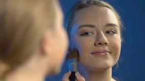 Uśmiechnięta dziewczyna stosuje wieczór makijaż, dosłania powietrza buziak odzwierciedlać, bezcelowość zbiory wideo