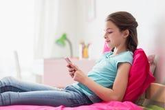 Uśmiechnięta dziewczyna texting na smartphone w domu Fotografia Stock
