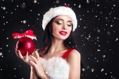 Uśmiechnięta dziewczyna trzyma czerwieni choinki piłki Kobiety na sukni i Santa ` s kapeluszu pomagier s Santa Atrakcyjna szczęśl Zdjęcia Royalty Free