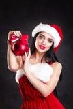 Uśmiechnięta dziewczyna trzyma czerwieni choinki piłki Kobiety na sukni i Santa ` s kapeluszu pomagier s Santa Atrakcyjna szczęśl Zdjęcie Stock