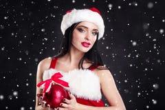 Uśmiechnięta dziewczyna trzyma czerwieni choinki piłki Kobiety na sukni i Santa ` s kapeluszu pomagier s Santa Atrakcyjna szczęśl Zdjęcia Stock