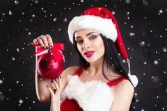 Uśmiechnięta dziewczyna trzyma czerwieni choinki piłki Kobiety na sukni i Santa ` s kapeluszu pomagier s Santa Atrakcyjna szczęśl Zdjęcie Royalty Free