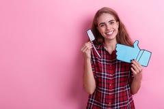 Uśmiechnięta dziewczyna trzyma papierowego kciuk i toothbrush kciuk up Na różowym tle obrazy stock