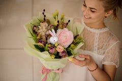 Uśmiechnięta dziewczyna trzyma pięknego wiosna bukiet oferta różowi i biali kwiaty zdjęcie stock