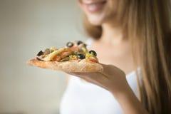 Uśmiechnięta dziewczyna trzyma plasterek pizza w jej ręce Zdjęcia Stock