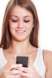 Uśmiechnięta dziewczyna używa mądrze telefon Fotografia Royalty Free