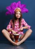 Uśmiechnięta dziewczyna w kapeluszu z piórkami siedzi na podłoga i rytmy bębnią zdjęcie royalty free