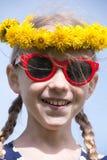 Uśmiechnięta dziewczyna w okularach przeciwsłonecznych i dandelion girlandzie obraz stock