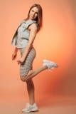Uśmiechnięta dziewczyna w pasiastej sukni i drelichowa kamizelki pozycja z jej nogą podnoszącą Fotografia Royalty Free