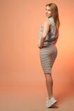 Uśmiechnięta dziewczyna w pasiastej sukni i drelichowej kamizelce trwanie z powrotem Fotografia Stock