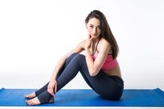 Uśmiechnięta dziewczyna w sportów ubraniach relaksuje po trenować na bławej macie Pojęcie sprawność fizyczna i aktywnego styl życ Obraz Royalty Free