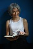 Uśmiechnięta dziewczyna w srebnej peruce leafing przez książki z bliska niebieska tła Zdjęcie Stock