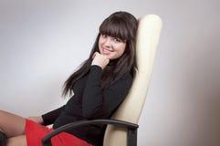 Uśmiechnięta dziewczyna w szefa krześle Obrazy Stock