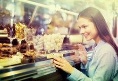 Uśmiechnięta dziewczyna wybiera czekolady obrazy stock