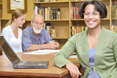 Uśmiechnięta dziewczyna z laptopem na stole Obraz Stock