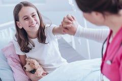 Uśmiechnięta dziewczyna z mokiet zabawką daje wysocy pięć pielęgniarka w szpitalu fotografia stock