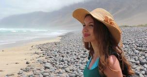 Uśmiechnięta dziewczyna z słomianym kapeluszem na plażowym przyglądającym falowanie oceanie na Caleta De Famara swobodny ruch zdjęcie wideo