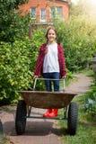 Uśmiechnięta dziewczyna z wheelbarrow pracuje przy ogródem przy słonecznym dniem obraz stock
