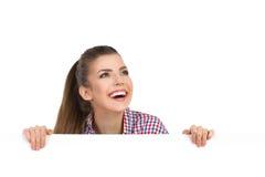 Uśmiechnięta dziewczyna Za plakatów spojrzeniami Przy niebem Obraz Stock