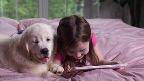Uśmiechnięta dziewczyny dopatrywania kreskówka na pastylce z szczeniakiem zdjęcie wideo