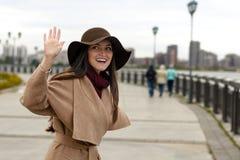 Uśmiechnięta elegancka dziewczyna w żakiecie z pasowym i dużym kapeluszowym falowaniem CZEŚĆ Pojęcie powitanie, kolegowanie, zaba obraz stock