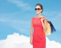 Uśmiechnięta elegancka kobieta w sukni z torba na zakupy Zdjęcia Royalty Free