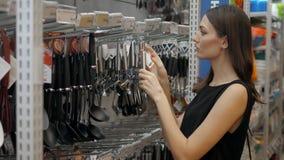 Uśmiechnięta europejska kobieta wybiera niecki w sklepowym cookware supermarkecie, szczęśliwa brunetki dziewczyna w sklepie zdjęcie wideo