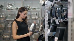 Uśmiechnięta europejska kobieta wybiera niecki w sklepowym cookware supermarkecie, szczęśliwa brunetki dziewczyna w sklepie zbiory